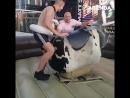 Пьяный мужик пытается оседлать механического быка