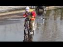 Мальчишки на велосипедах рассекают весенние лужи