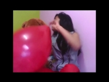 Girl blows to pop a red balloon