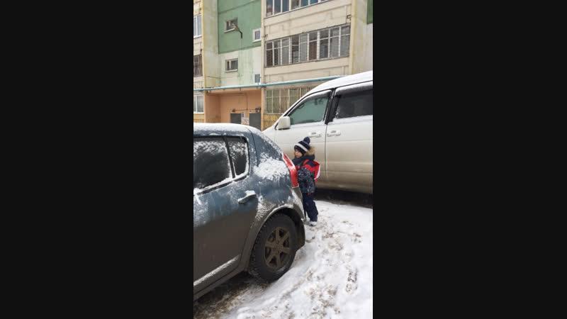 Миша очищает машину от снега
