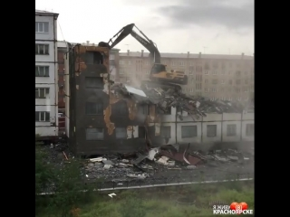 В Норильске эскаватор сносит здание стоя на нём