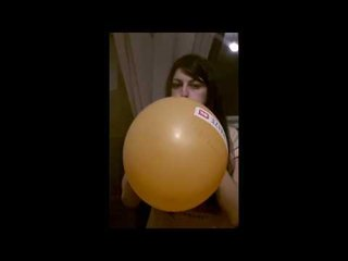Scared girl blows to pop orange balloon