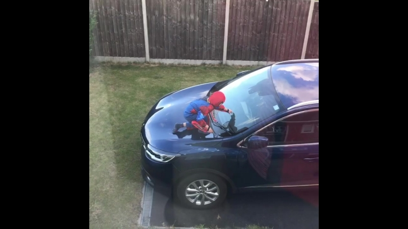 Little lad in a spider man costume climbs on his parents car and shoots webs