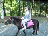 Танюша катается на пони по имени Миша.