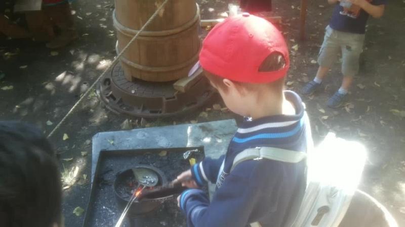 Сын помогает в полевой пулелитейной мастерской 17 века на фестивале Времена и Эпохи