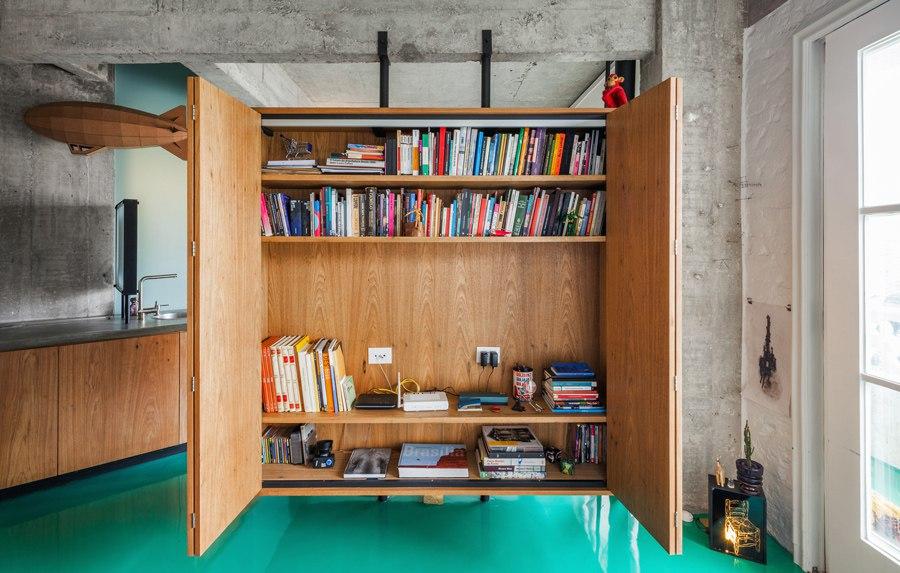 Интерьер квартиры 46 м с бетонными стенами, ярким наливным полом и парящим шкафом-перегородкой в Бразилии.
