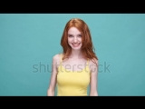 stock-footage-smiling-redheaded-girl-playing-hide-and-seek-while-covering-her-eyes-with-palms-isolated-over-blue