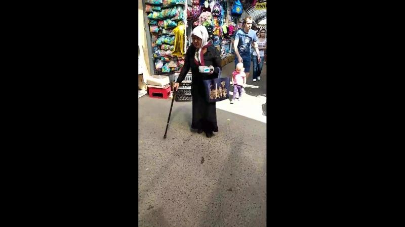 Ряженая монашка поёт какие-то песни и побирается на Экспобеле
