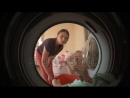 Stock footage young mother with her beautiful little child loads laundry in drum of washing machine bathroom