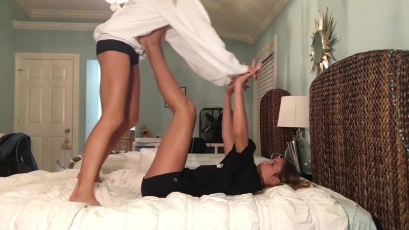 Две девушки занимаются гимнастикой на кровате.