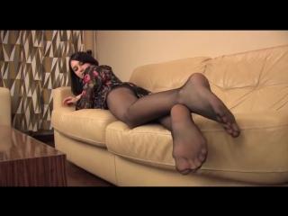 Студентка в колготках с длинными ногами лежит на диване и показывает ножки и попку и трусики