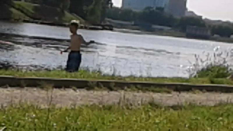 Управляемый маленький водный катерок плавает под чьим-то управлением с радиопульта на поверхности Джамгаровского пруда.