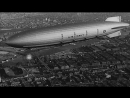 Dirigible USS Akron during its first flight over buildings, river bridges and Stock Footage