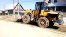 Фронтальный погрузчик ровняет грунт на улице Ушакова в Бердске