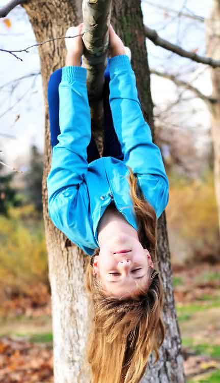 Гиперактивный ребенок висит вверх ногами с дерева
