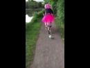 Lad with pink wig and skirt rides bike down path