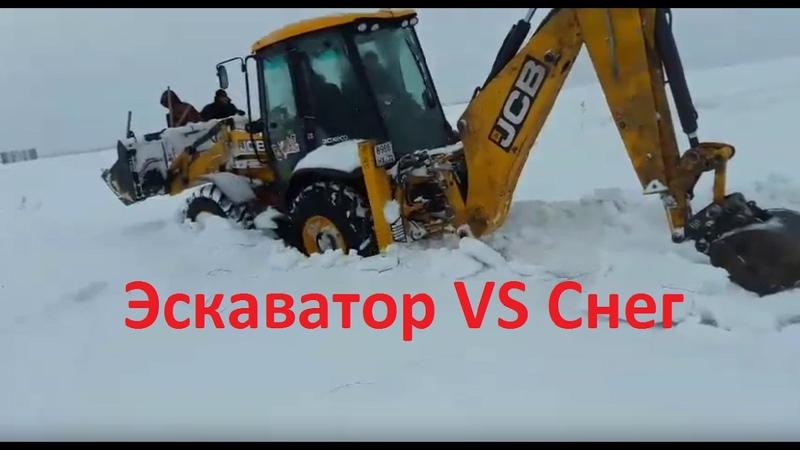 Трактор (экскаватор) JCB пробирается через метровый снег.