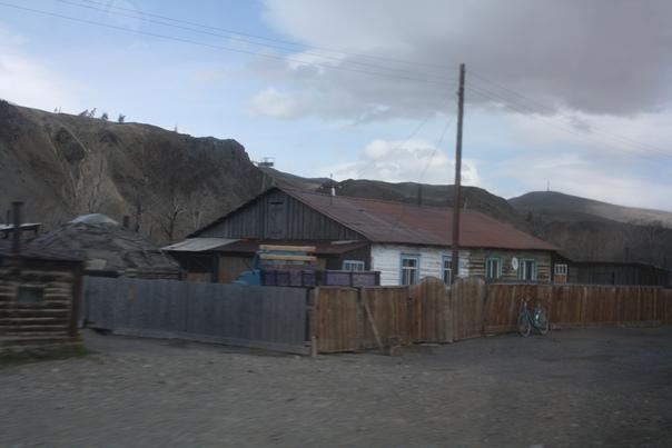 Сверху дверца, видимо, хранят сено зимой. А слева крыша напоминает Аил. Интересно, что свежий забор справа более кривой, чем старый слева.