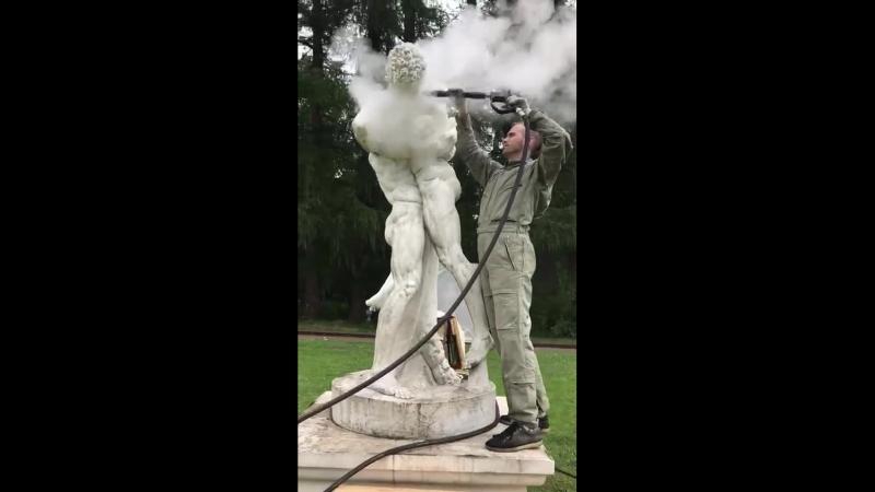Скульптурная группа «Антей и Геркулес» на верхней террасе итальянского парка обрабатывается паром...