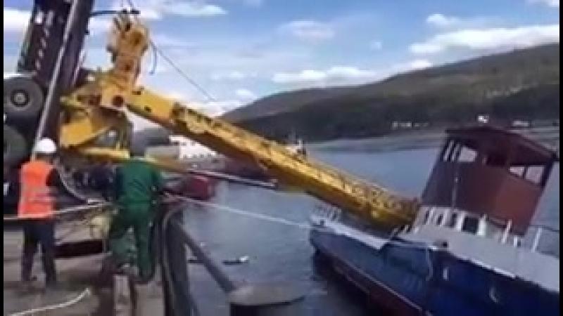 В городе Усть Кут в Иркутской области тяжелый автокран спускал в реку Лену небольшое судно Из за противовеса 50 тонный кран оп