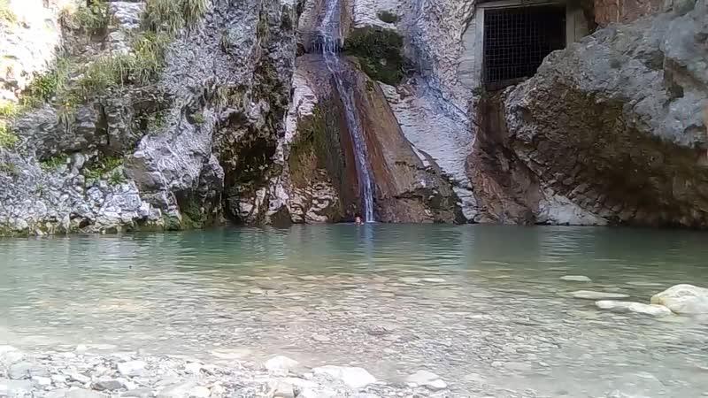 Пловцы в горном озере с водопадом