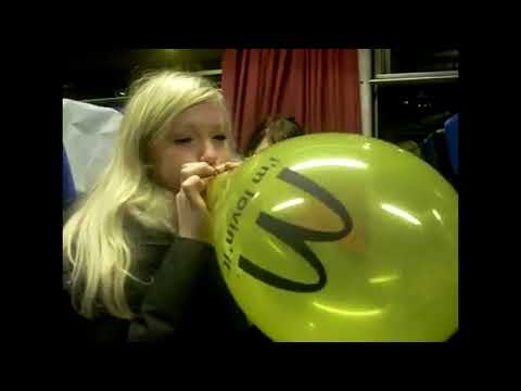 Girl blows to pop a yellow balloon in a bus