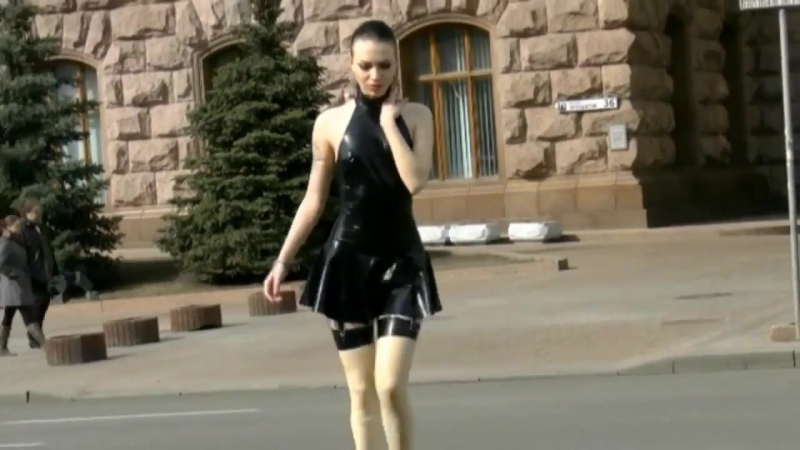 Sexy girl is showing her body in latex mini dress and stockings in public