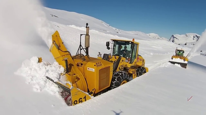 Мощная снегоуборочная техника пробивается сквозь глубокий снег