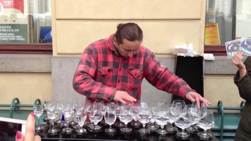 Уличный музыкант виртуозно играет на бокалах с водой.720