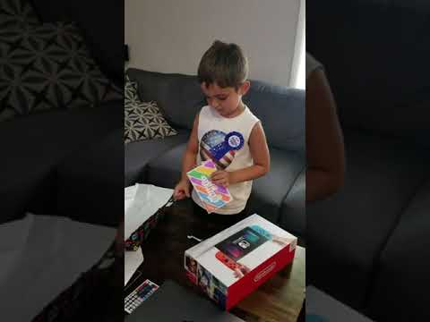 Excited Little Boy Unwraps Video Game Console for Birthday - 994156