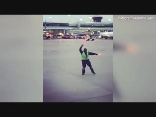 Toronto airport worker entertains child by dancing next to plane