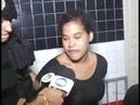 Mulher presa tenta morder microfone de repórter