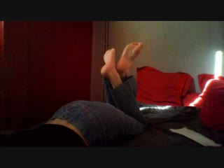 Girl is lying on the bed, lifting her feet and soles right in front of the camera))
