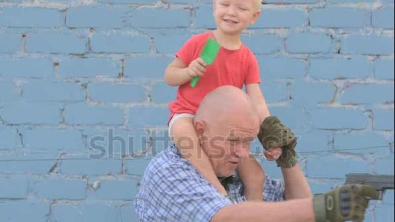 Stock-footage-elderly-man-with-shaved-head-wearing-sunglasses-is-holding-small-child-and-gun-in-his-hands-boy-is