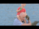 Stock footage elderly man with shaved head wearing sunglasses is holding small child and gun in his hands boy is