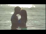 The Couple pair Walk On The Beach And Hug And Kiss In The Water