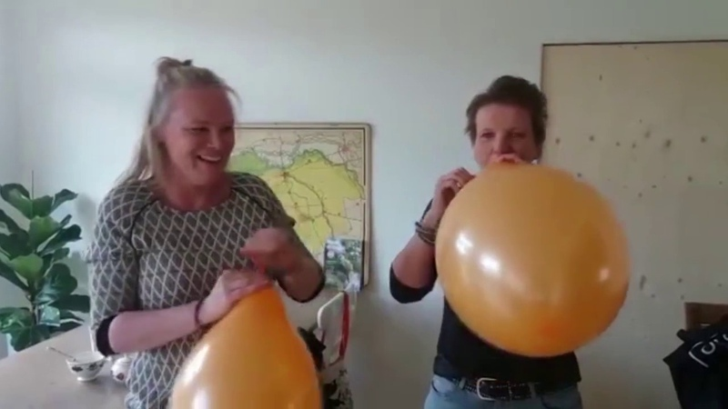 Two woman battle it out in a blow to pop race with orange balloons