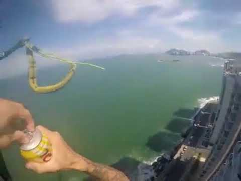 Paraglider Grabs Beer From Guy on Rooftop Balcony