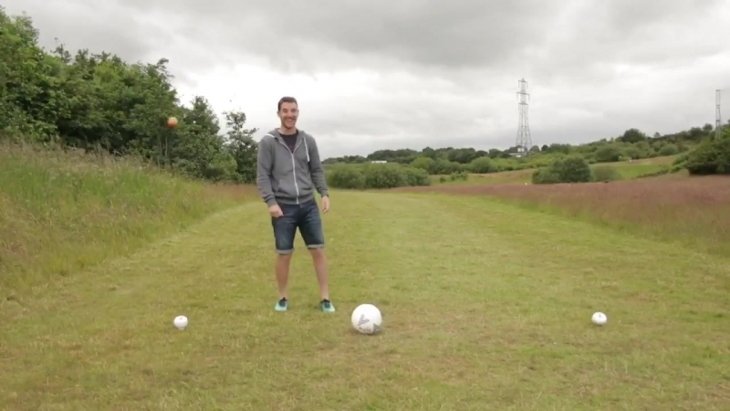 Lad throws football at football his mate is trying to kick