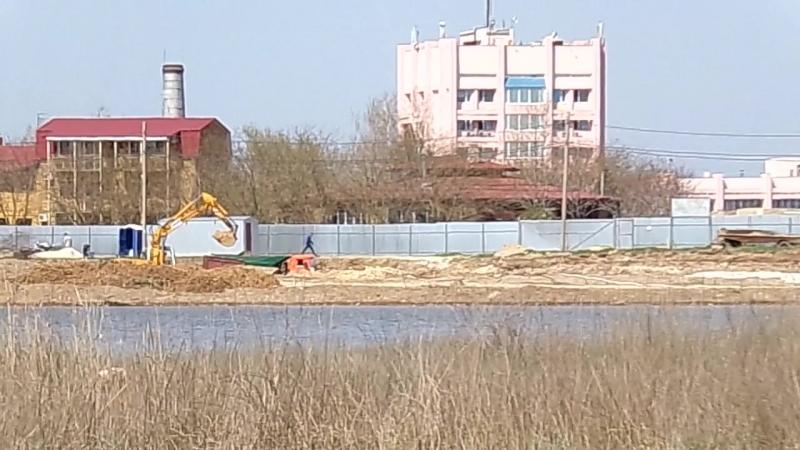 Роют котлован под фундамент на берегу озера