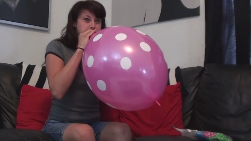 Girl blows up a pink dotted link balloon so big it pops awesome