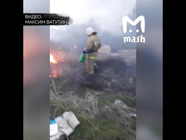 Пожарный тушит пожар из пластиковой лейки