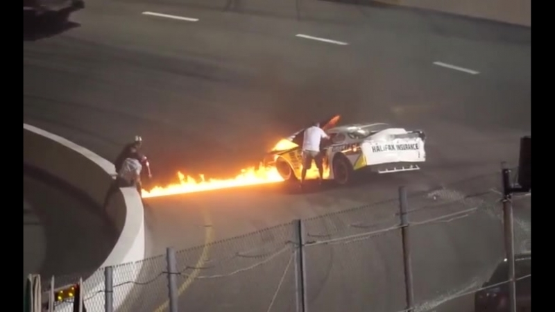 Dad rushes on the track to free his son from burning racecar