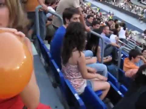 Girl blow to pop orange balloon in stadium Looners Paradise