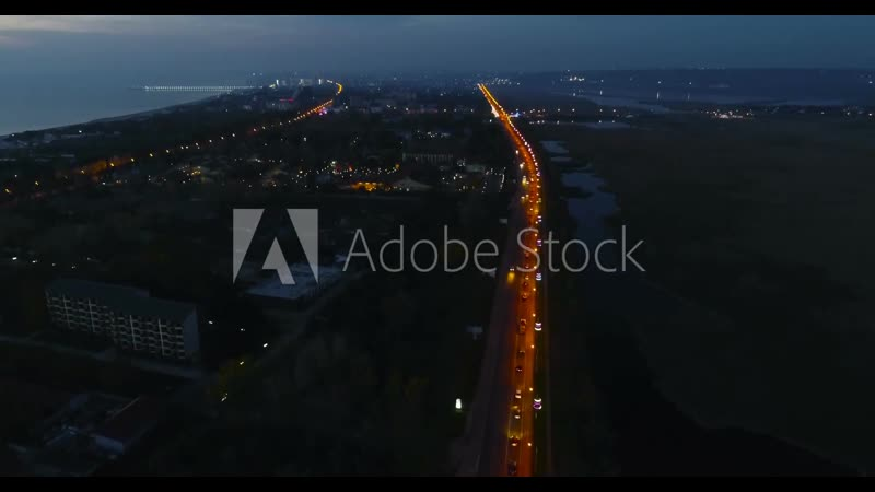 Beautiful night view of coastal city with roadway and wet meadows