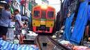 The Train passes through the MaeKlong Railway Market / Поезд едет по товару на железнодорожном рынке
