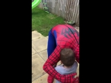 Spider-man climbs over a fence and gives a little boy a hug and a birthday prese