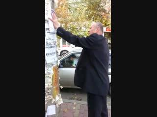 Вандал занимается незаконной расклейкой рекламы. Челябинск. сентябрь 2018