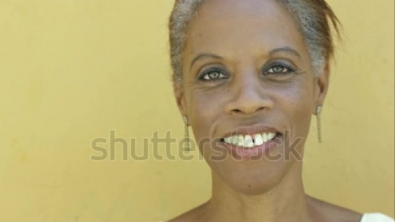 Portrait Of Black 50 Year Old Surprised Woman With White Hair, Smiling On Yellow Background Stock