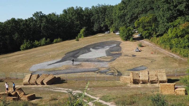 Французский художник рисует биокартину сажей и известью на траве в Центральном парке